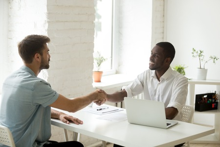 Photo for African and caucasian businessmen shaking hands over office desk, satisfied white partner closing successful business deal with black investor, handshake after making agreement or getting hired - Royalty Free Image