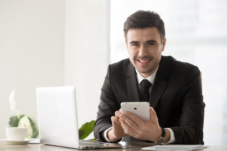 Foto für Portrait of handsome businessman sitting at desk in front of laptop, using digital tablet and looking at camera with happy smile. Company financial director communicating with business partners online - Lizenzfreies Bild