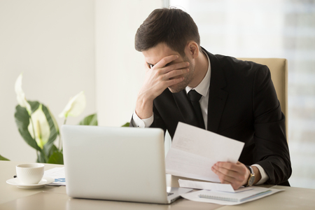Photo pour Businessman shocked with bad news in letter, upset because of loan refusal, feeling suppressed when receiving notification about company bankruptcy or debts to bank. Depression through work dismissal - image libre de droit