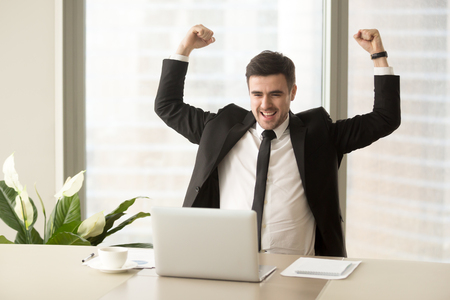 Photo pour Millennial businessman raising hands and happily yelling when looking on laptop at desk. Business leader feeling positive because of successful deal confirmation, excited with great result in work - image libre de droit
