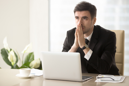 Photo pour Worried company leader thinking about problem solution, pondering important question, frustrated because of difficulties in business while sitting at desk. Religious businessman praying at workplace - image libre de droit