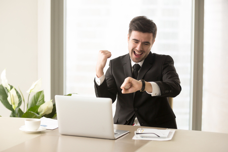 Photo pour Excited businessman yelling with joy when sitting at desk in front of laptop and looking at wrist watch. Happy office worker finishing work before deadline, glad because of ending of working day - image libre de droit