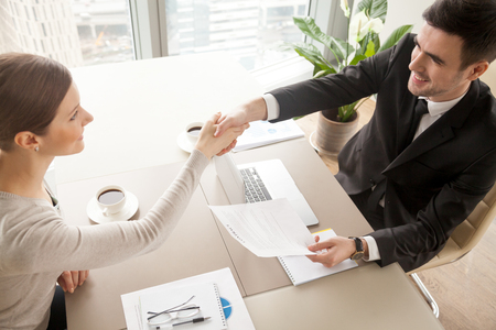Photo for Smiling female and male business leaders handshaking over desk after or before signing contract in office. Happy businesswoman congratulating businessman with concluding profitable agreement. Top view - Royalty Free Image