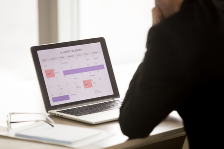 Foto de Back over shoulder view of businessman sitting at desk in front of laptop with work schedule on screen. Company manager using calendar app planning work tasks and priorities in business for next month - Imagen libre de derechos