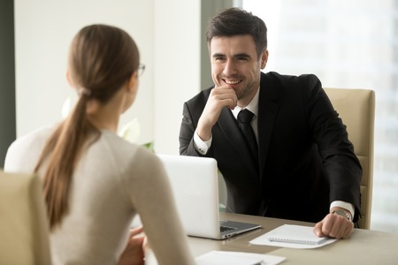 Photo for Handsome smiling male office worker in business suit sitting at desk with laptop in front of female colleague. Happy businessman talking with secretary. Positive first impression on job interview - Royalty Free Image