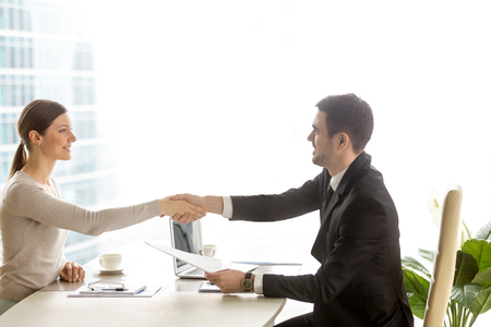 Photo for Male human resources manager holding resume and welcoming with handshake female job candidate in company office. Business partners agreeing with terms of contract. Successful negotiation. Side view - Royalty Free Image