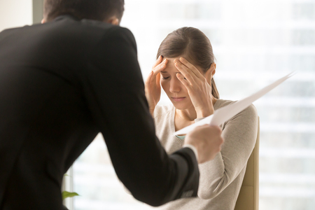 Photo pour Stressed millennial woman listening claims of angry boss on mistakes in report. Frightened by prospect of dismissal female office worker worried because of serious fail in work. Scandalous, mad client - image libre de droit