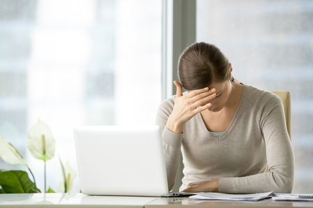 Photo for Stressed and tired female employee suffering of headache while sitting at desk in front of laptop. Frustrated nervous businesswoman struggling with tension during work day, thinking hard about problem - Royalty Free Image