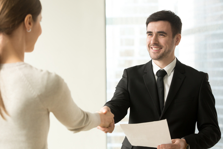 Photo for Smiling male manager with contract document in hand handshaking with female client or business partner in company office. Happy businessman welcoming businesswoman before negotiations - Royalty Free Image
