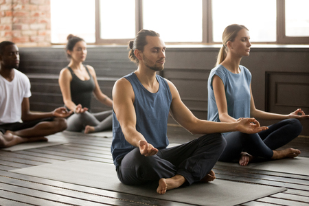Photo pour Group of young sporty people practicing yoga lesson, sitting in Sukhasana exercise, Easy Seat pose with mudra gesture, students working out in club, indoor, studio - image libre de droit