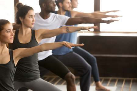 Photo for Group of young sporty afro american and caucasian people practicing yoga lesson, standing in Warrior two exercise, Virabhadrasana II pose, working out, indoor close up, studio - Royalty Free Image
