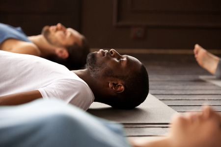 Photo pour Group of young afro american and caucasian sporty people practicing yoga lesson lying in Dead Body or Corpse pose, Savasana exercise, resting after practice, working out, indoor close up, studio - image libre de droit