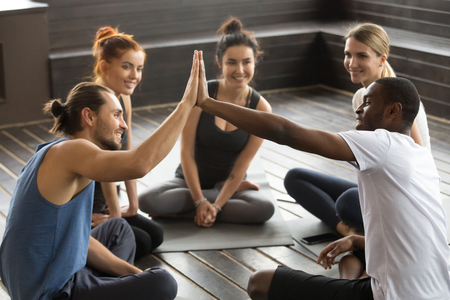 Photo for Smiling diverse yoga team members giving high five at group class, fit sporty young african and caucasian men join hands happy to train together supporting encouraging motivation for fitness teamwork - Royalty Free Image