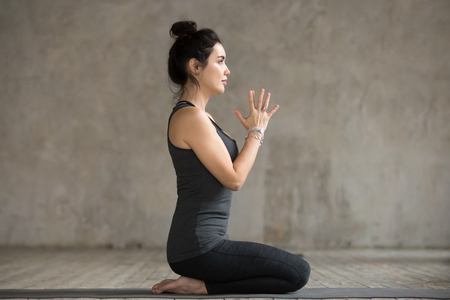 Photo pour Young woman practicing yoga, doing seiza exercise, vajrasana pose, working out, wearing sportswear, black pants and top, indoor full length, gray wall in yoga studio - image libre de droit