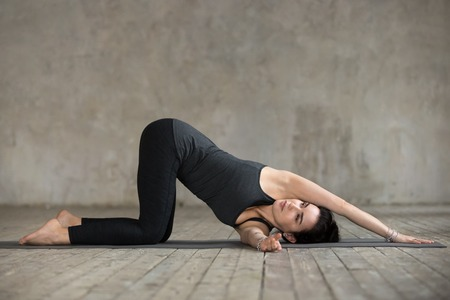Photo pour Young sporty woman practicing yoga, doing thread the needle exercise, spine bend pose, working out, wearing sportswear, black pants and top, indoor full length, gray wall in yoga studio, side view - image libre de droit