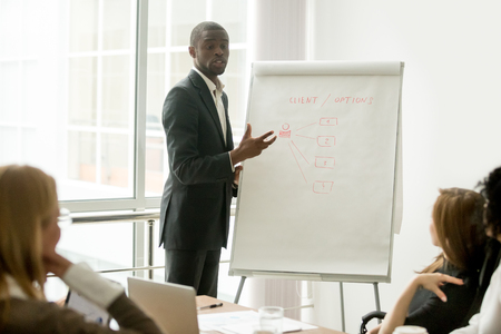 Photo pour Confident african speaker gives presentation to multiracial sales team with flipchart, black businessman in suit presenting new marketing project speaking at seminar, business coach training managers - image libre de droit
