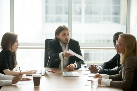 Foto de Angry boss reprimanding female employee for bad work result sitting at conference table, male ceo scolding incompetent manager blaming for mistake in financial report or failure at team group meeting - Imagen libre de derechos
