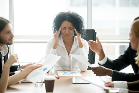 Photo for Stressed overwhelmed african businesswoman feels tired at corporate meeting, exhausted black female boss suffering from headache touching temples at team briefing, stress at work or migraine concept - Royalty Free Image