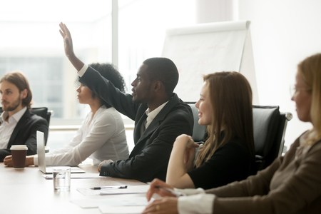 Foto de African american businessman raising hand at diverse team meeting, black training participant listener man asks question during business seminar sitting at conference table, corporate group education - Imagen libre de derechos
