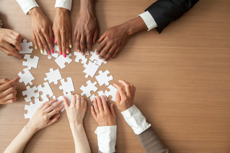 Photo for Hands of multi-ethnic team assembling jigsaw puzzle, multiracial group of black and white people joining pieces at desk, successful teamwork concept, help and support in business, close up top view - Royalty Free Image