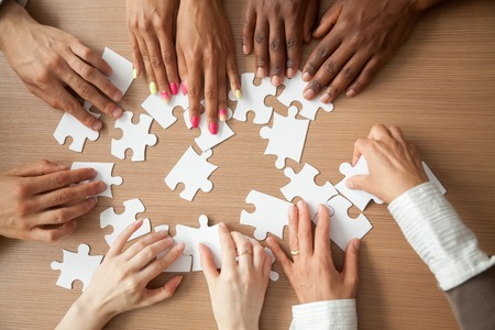 Foto de Hands of diverse people assembling jigsaw puzzle, african and caucasian team put pieces together searching for right match, help support in teamwork to find common solution concept, top close up view - Imagen libre de derechos