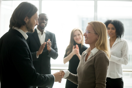 Photo for Boss handshaking employee congratulating with promotion while diverse colleagues clapping applauding, company ceo awarding appreciating motivating office worker for good work result by shaking hands - Royalty Free Image