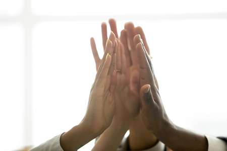 Foto de Motivated multiracial business team join hands palms together, black and white diverse people group give high five as concept of successful teamwork and help support unity in common goal achievement - Imagen libre de derechos