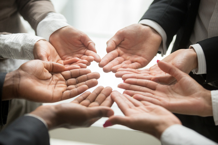 Photo pour Diverse multi-ethnic business team members join helping hands group together palms up as concept of involvement, contribution in common goal, supporting unity and crowdfunding donation, close up view - image libre de droit