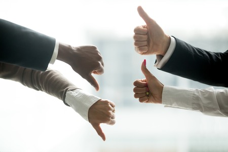Foto de Hands of diverse business people showing thumbs up and down, like versus dislike gesture, positive negative feedback, yes and no opposition voting, confrontation disagreement at negotiations concept - Imagen libre de derechos
