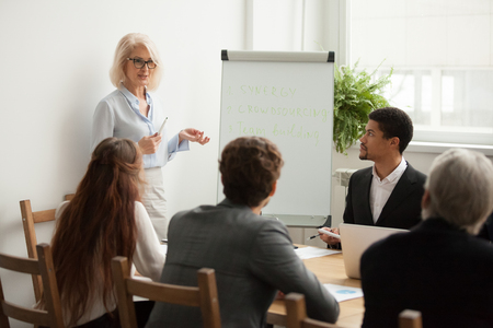 Foto de Aged attractive businesswoman giving presentation at corporate diverse group meeting, senior female business coach, woman boss or team leader presenting new strategic plan to multiracial employees - Imagen libre de derechos