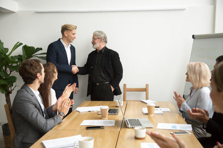 Photo for Senior gray-haired businessman boss promoting male employee thanking appreciating good work shaking hands while team applauding congratulating at group meeting, trust, recognition, support concept - Royalty Free Image