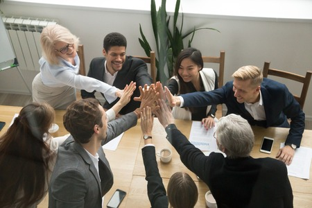 Foto de Diverse motivated multi-ethnic business team giving high five showing unity concept, young and old corporate group join hands promising support in collaboration, help commitment in teamwork, top view - Imagen libre de derechos