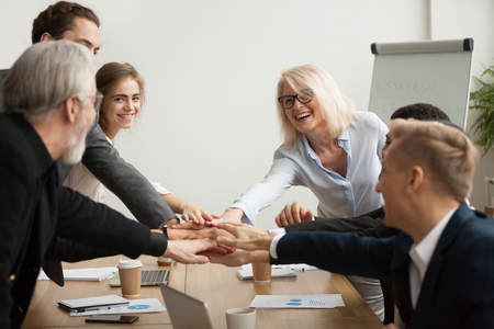 Photo for Happy smiling corporate team of senior executives and young employees join hands together at group meeting, business people celebrating success achievement unity, promising help support in teamwork - Royalty Free Image