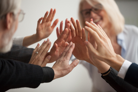 Foto de Hands of diverse business people giving high five, smiling team members, teachers and students promising help unity in goal achievement, coaching support in mentoring teamwork concept, close up view - Imagen libre de derechos