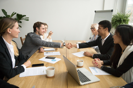 Photo for Diverse businessmen shaking hands after signing contracts at group multiracial meeting, african and caucasian partners in suits handshaking promising good deal after successful negotiations concept - Royalty Free Image