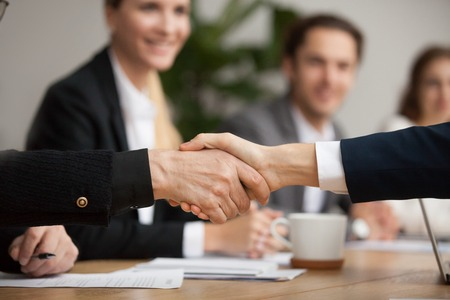Photo for Hands of senior and young businessmen shaking at group meeting, two partners of different age handshaking making agreement or good deal, concluding contract help support concept, close up view - Royalty Free Image