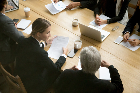 Photo for Negotiations concept, different businesspeople discussing deal details at group meeting, young and senior partners team thinking talking consulting about contract sitting at conference office table - Royalty Free Image