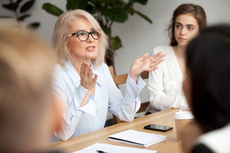 Photo pour Attractive aged businesswoman, teacher or mentor coach speaking to young people, senior woman in glasses teaching audience at training seminar, female business leader speaker talking at meeting - image libre de droit