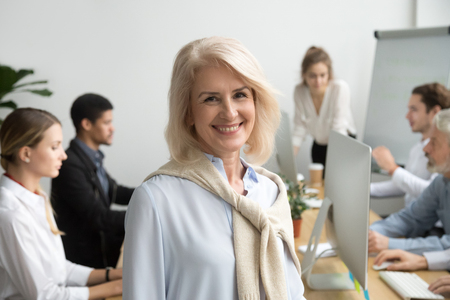 Photo for Smiling female aged company executive or team leader looking at camera, happy senior businesswoman teacher coach posing with office people at background, friendly older woman boss head shot portrait - Royalty Free Image