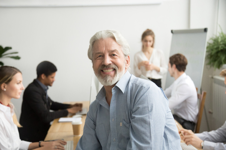Photo pour Smiling male senior team leader, aged teacher looking at camera with office people at background, happy old gray-haired company boss, experienced mentor or executive professional head shot portrait - image libre de droit