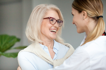 Photo pour Beautiful aged woman in glasses embracing young adult lady and laughing, smiling attractive senior older mother happy to hug grown-up daughter, warm sincere family bonding having fun together - image libre de droit