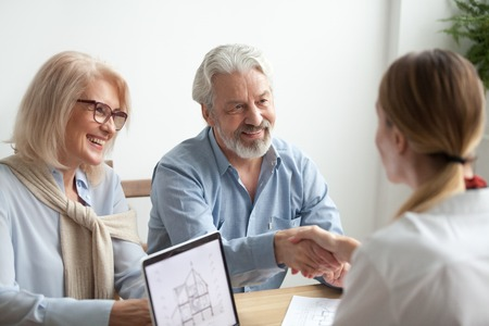 Photo pour Smiling satisfied senior couple making sale purchase deal concluding contract handshaking real estate agent or realtor, happy older family and broker shake hands agreeing to buy new house at meeting - image libre de droit