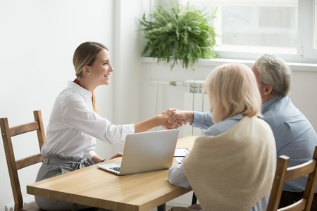 Photo for Smiling female lawyer, real estate agent or financial advisor handshaking older senior couple, insurance broker and aged family shake hands making purchase deal, investment or greeting at meeting - Royalty Free Image