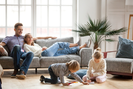 Foto de Children sister and brother playing drawing together on floor while young parents relaxing at home on sofa, little boy girl having fun, friendship between siblings, family leisure time in living room - Imagen libre de derechos