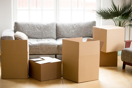 Photo pour Cardboard carton boxes with personal belongings household stuff in modern living room, many packed containers on moving day in new home, relocation or house removals delivery service concept - image libre de droit