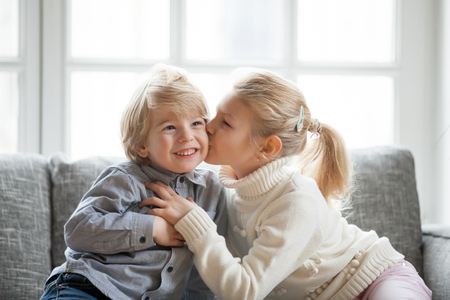 Photo pour Older sister embracing little younger brother at home, kid girl kissing cute shy smiling preschool boy on cheek, happy children having fun together, love and friendship between siblings concept - image libre de droit