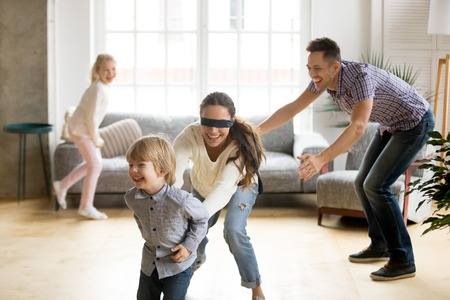 Photo for Blindfolded mother catching little son playing hide and seek at home, happy children having fun with mom and dad, parents with kids spending time together in living room, weekend family games concept - Royalty Free Image