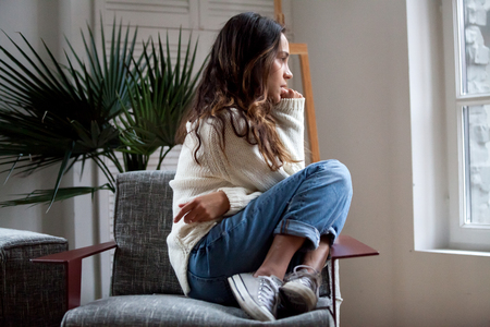 Photo pour Sad thoughtful teen girl sits on chair feels depressed, offended or lonely, upset young woman suffers from abuse, harassment or heartbreak, grieving lady or violence victim has psychological problem - image libre de droit