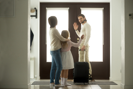 Foto de Smiling father waves goodbye to wife and daughter leaves home for business trip stands at door with travel suitcase, kid girl stays with mom seeing off dad moving out after divorce, family separation - Imagen libre de derechos