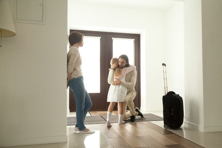 Photo for Little kid girl embracing dad leaving family moving out with travel case, sad daughter hugging father in house hall saying goodbye to daddy going away, unhappy child of divorced parents concept - Royalty Free Image